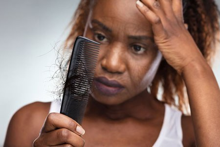 Cancer Treatment - Frustrated Black Female Losing Hair in a Comb